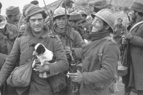 7-george-orwell-tiene-un-cucciolo-durante-la-guerra-civile-spagnola-nel-1937-ernest-hemmingway-nello-sfondo.jpg